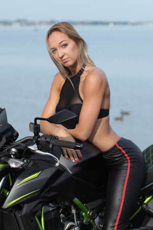 young woman with a sports motorcycle on sea background