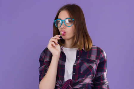 blue background: Young pretty girl with lollipop, happy and cute