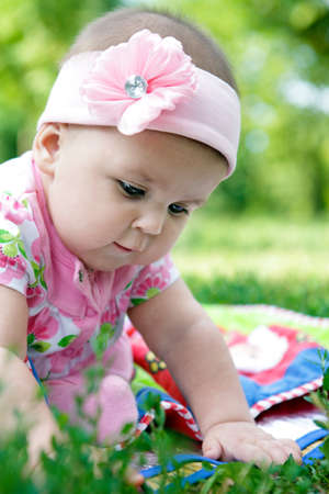 cute baby-girl outdoors playing on a grass