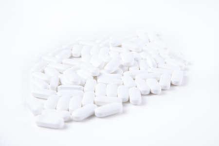 High key shot of white pills brightly lit on white background