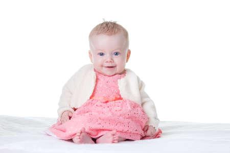 Little cute baby-girl in pink dress, sitting, isolated 版權商用圖片