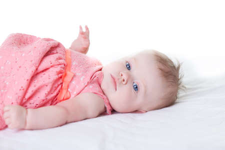 Cute baby-girl in pink dress, on her back isolated