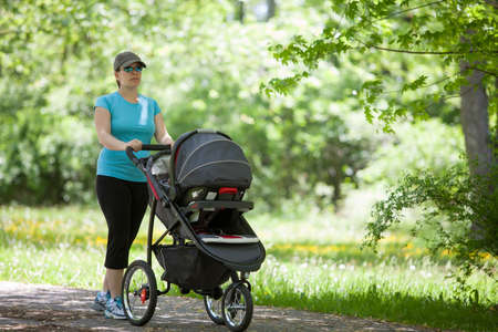 Young mother pushing a stroller in the park photo