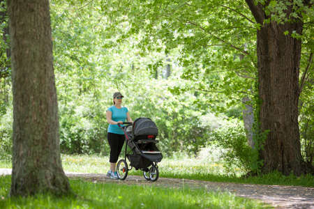 Young mother pushing a stroller in the park