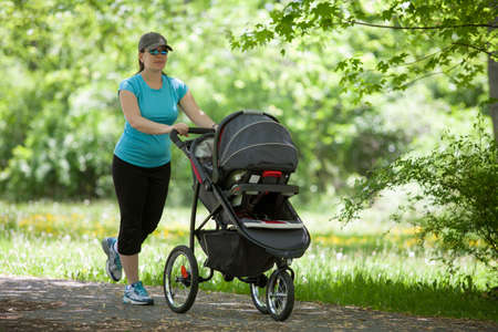 Young mother running while pushing a stroller in the park