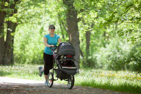 baby carriage: Young mother running while pushing a stroller in the park
