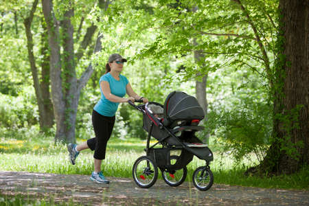Young mother running while pushing a stroller in the park photo