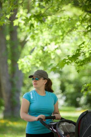 유모차와 함께 공원에 서있는 젊은 어머니