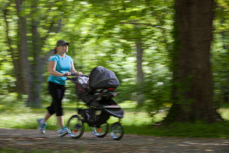 Young mother running while pushing a stroller in the park, panning photo
