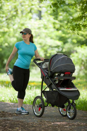 Young woman stretching next to stroller in the park