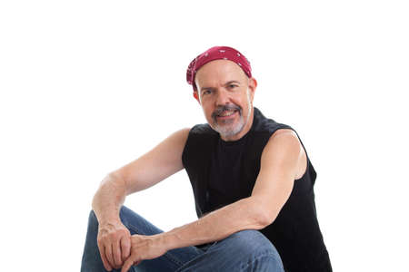 Mature biker in red  bandana sitting on the ground, isolated on white