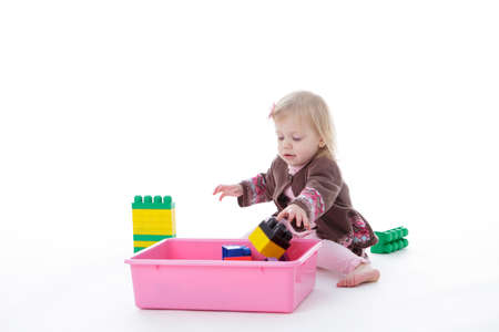 toddler girl picking up toys in pink bin, isolated on white background
