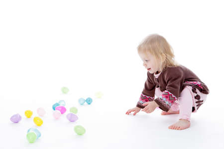 toddler: Little girl playing with Easter eggs, isolated on white background