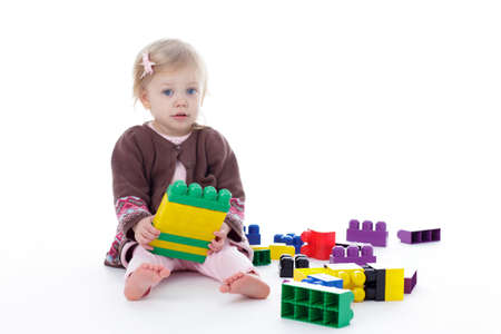 sweater girl: toddler girl playing with colored building blocks, holding in hands, isolated on white background