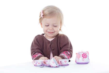blonde blue eyes: toddler girl playing with tea set, isolated on white background Stock Photo