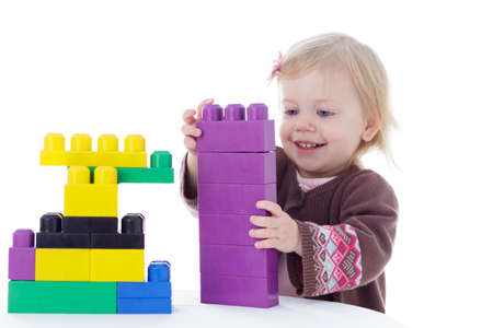 and blocks: toddler girl playing with colored building blocks, holding in hands, isolated on white background