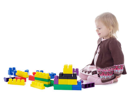 lazo rosa: toddler girl playing with colored building blocks, isolated on white background