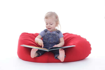 toddler girl in overalls, reading a book, sitting on a bean bag, isolated on white