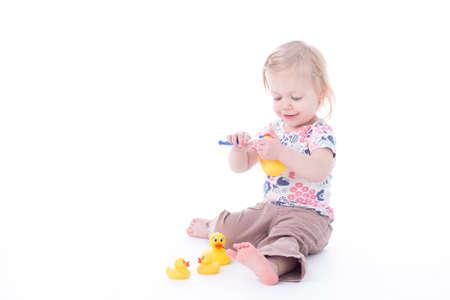 khaki pants: toddler girl brushing duck teeth, isolated on white Stock Photo