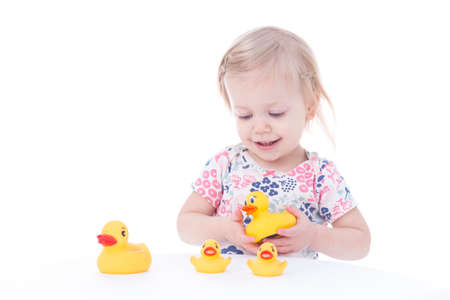 toddler girl playing with ducks, isolated on white Stock Photo