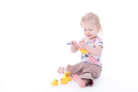toddler girl brushing duck teeth, isolated on white Stock Photo