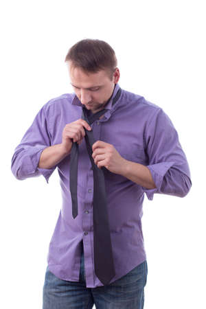 Man tying a tie, in long sleeved shirt, isolated on white Imagens