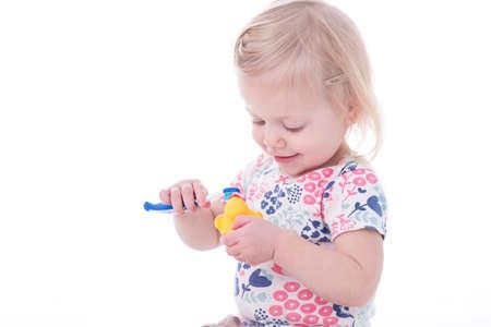 pantalones abajo: niña niño cepillarse los dientes pato, aislado en blanco Foto de archivo
