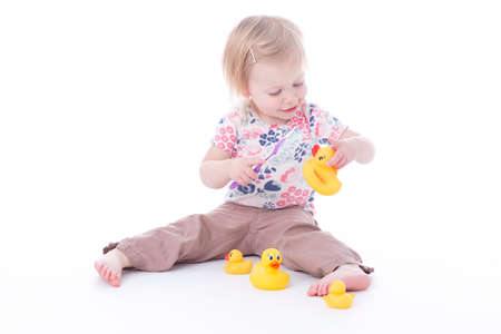 pants down: toddler girl brushing duck teeth, isolated on white Stock Photo