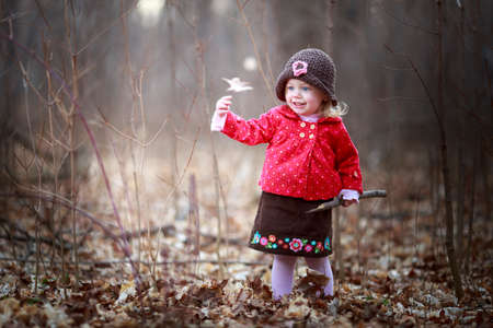 happy little child, baby girl laughing and playing in the fall outdoors
