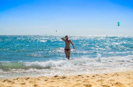 Back view of sexy young lady in bikini wavy sea