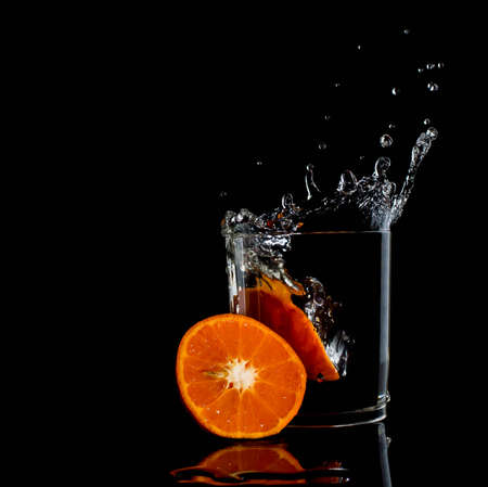 Water in glass with water splash with tangerine energy clear Stock Photo