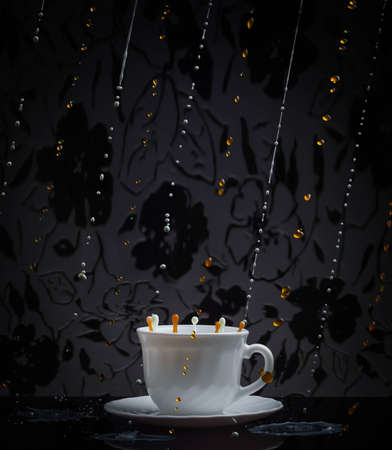 Splash of coffee and milk in white cup isolated on black background Imagens