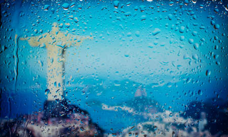 The statue of Christ the Redeemer in Rio de Janeiro, Brazil A view of the city from a window from a high point during a rain. Rain drops on glass. Focus on drops