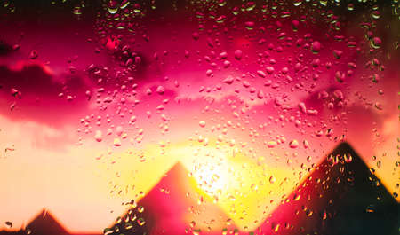 The Egyptian pyramids A view of the city from a window from a high point during a rain. Rain drops on glass. Focus on drops Imagens