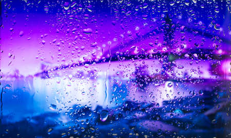 A view of the city from a window from a high point during a rain. Rain drops on glass. Focus on drops