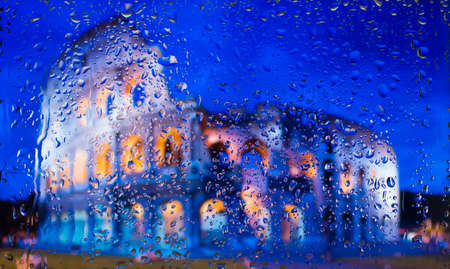 Colosseum of Rome - Might and Glory of Ancient Rome. A view of the city from a window from a high point during a rain. Rain drops on glass. Focus on drops Stock Photo