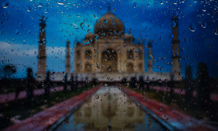 wonder of the world Taj Mahal. A view of the city from a window from a high point during a rain. Rain drops on glass. Focus on drops