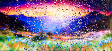 Mountains and field of flowers A view of the city from a window from a high point during a rain. Rain drops on glass. Focus on drops Imagens