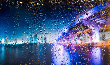 bridge A view of the city from a window from a high point during a rain. Rain drops on glass. Focus on drops