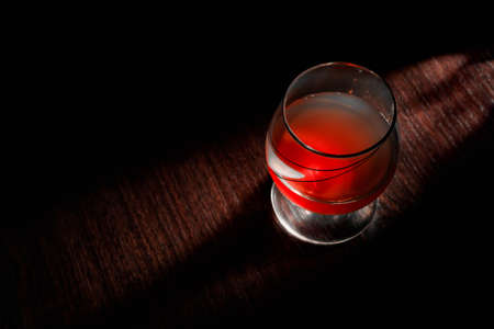 Glass of whiskey with smoking cigar and ice cubes on wooden table bar, wine, luxury
