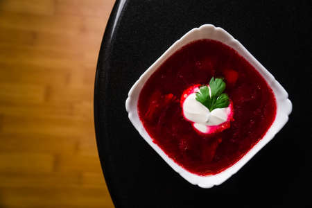 Borscht. Red soup in bowl with sour cream, isolated on wooden background. Close-up. Top view vegetable, vegetarian, vintage, white, copyspace