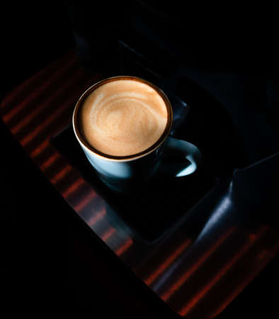 Splash of coffee and milk in white cup isolated on black background movement action arabica, aroma, aromatic