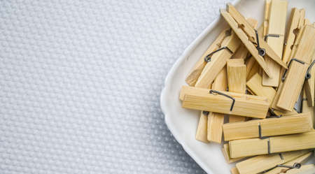 clothespins in a plate or bowl, on a white and black background, on a rope, new, wooden, boke Imagens