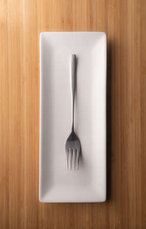 an elegant fork on an elongated plate, on a bamboo table, a cutlery is designed for pricking food, and it s a bird. designer things, fashion, fashion beauty. Many yellow plasic forks and spoons on black background, top view. Disposable table wear concept Imagens