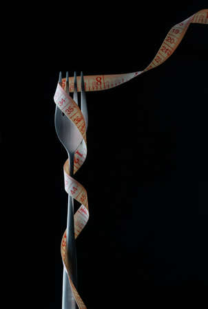 Fork and measuring tape in hand and plate isolated on white food, fitness, nutrition, healthy, dieting, slim, diet, health, fork, meter, loss centimeter