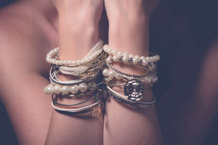 Collection of bracelets on the hands of a woman Stock Photo