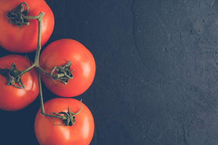 kinfolk: Fresh red tomatoes on a dark stone background Stock Photo