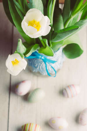 White tulips and Easter eggs on white wooden background. The concept of Easter or spring Stock Photo