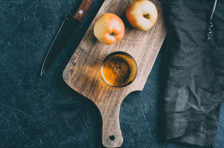 Apple cider in a glass and fresh apples on dark stone background. Copy space for text or design Stok Fotoğraf