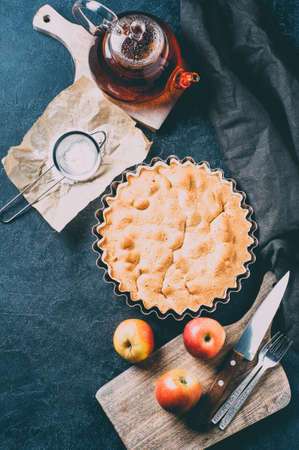 Apple pie, fresh apples and a pot of tea over dark concrete background. Vertical cropped
